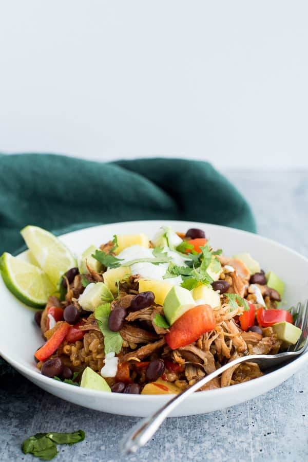 jerk chicken in a bowl topped with tomatoes, yogurt, and avocados