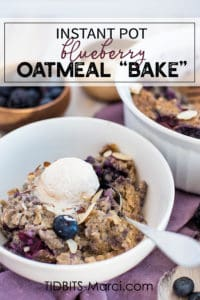 blueberry oatmeal in a white bowl with cream on top