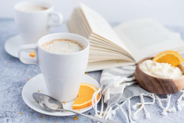 Chocolate drink in a white cup with cream and orange slices