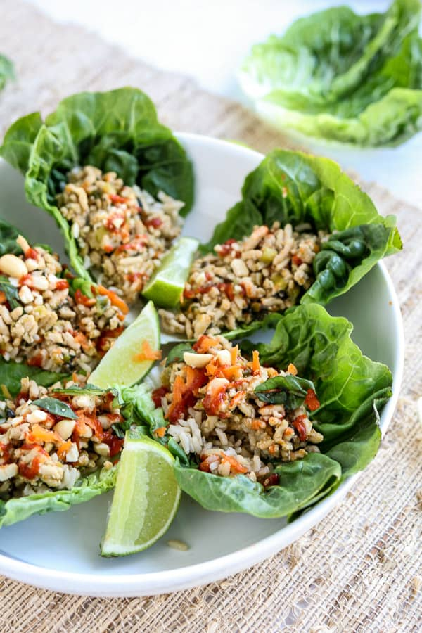 Instant Pot Asian Chicken Lettuce Wraps on a white plate with limes