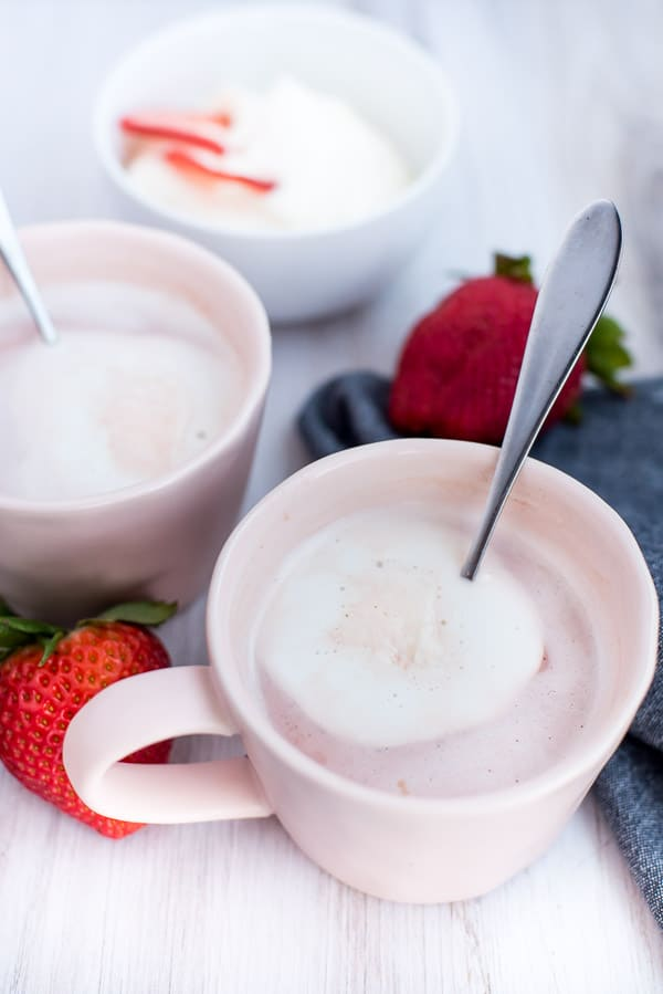 Instant Pot Strawbery Crio Bru in a pink cup with cream on a wood board with strawberries