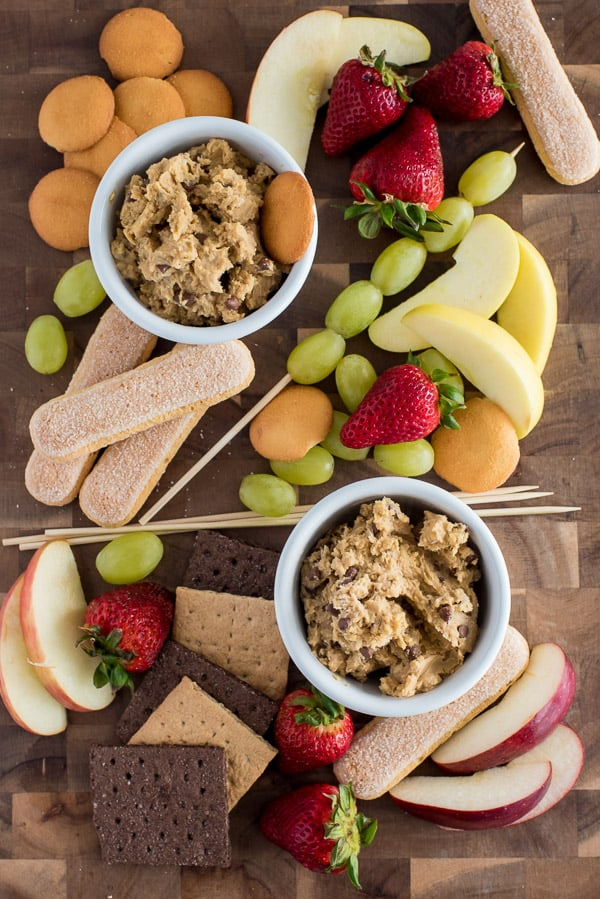 White bowls filled with healthy cookie dough surrounded by fruit and crackers