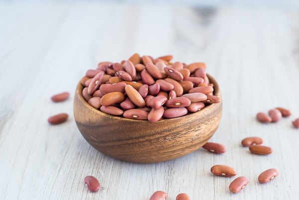 dried beans in a wood bowl on a white table