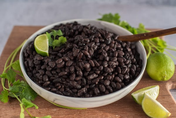 Instant Pot Black Beans in a white bowl with a lime wedge