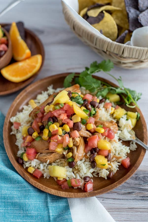 Instant Pot Orange Chicken with Mango Black Bean Salsa over rice on a wood plate
