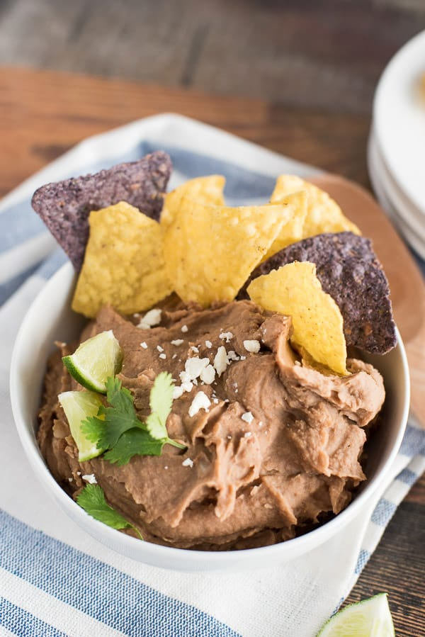 instant pot refried beans in a white bowl with chips and lime wedges