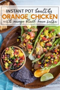 Instant Pot Orange Chicken with Mango Black Bean Salsa in lettuce wraps on a wood plate
