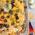 Plate of 7 layer bean dip with cheese and olives on top