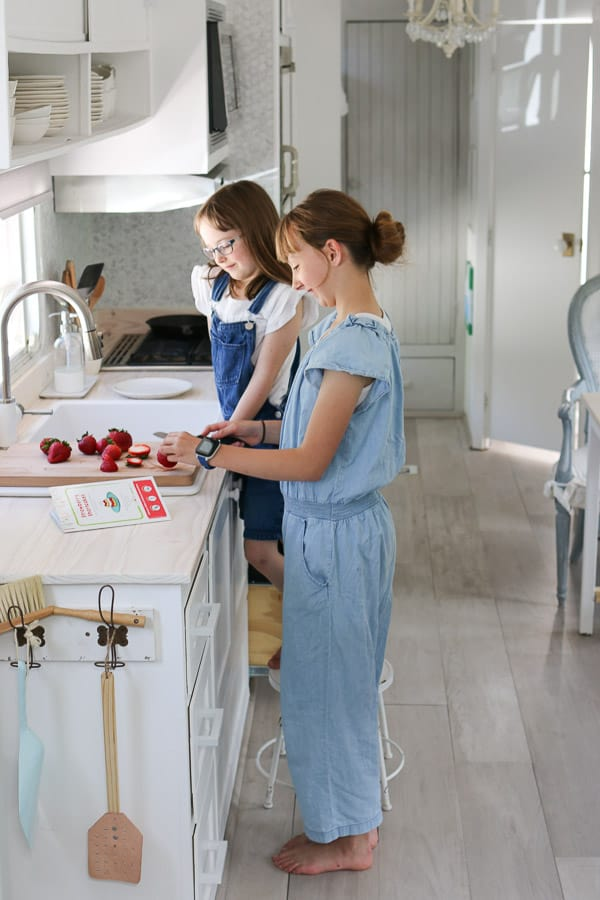 two girls cutting strawberries