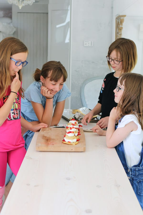 four girls looking at strawberry shortcakes on a wood board