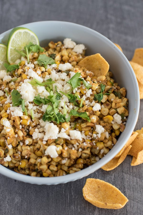 Large bowl of Mexican Street Corn Salad with cheese and lime wedges