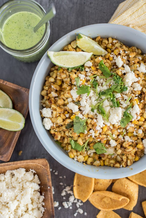Mexican Street Corn Salad topped with cheese and lime wedges in a bowl