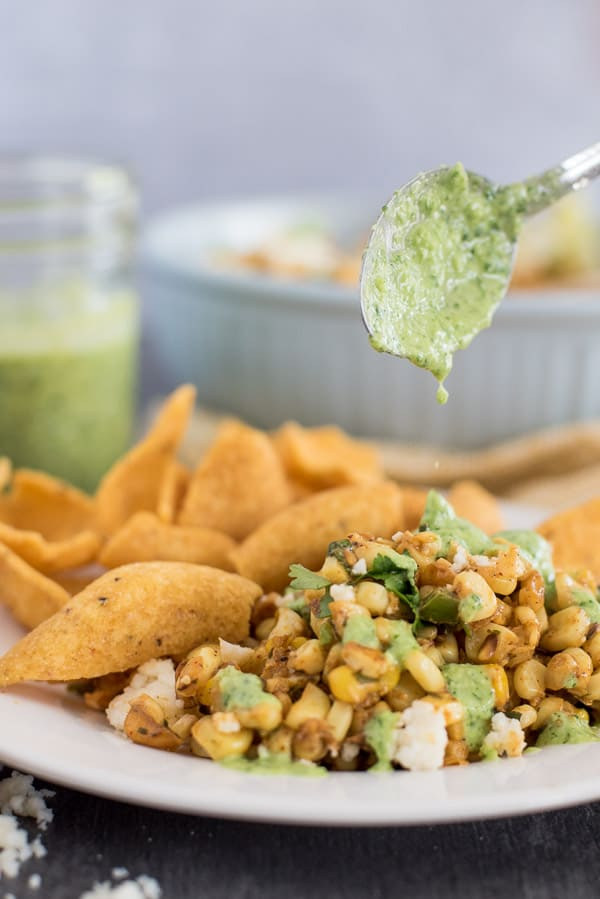 Mexican Street Corn Salad on a white plate with a side of corn chips with a drizzle of jalapeno cream sauce