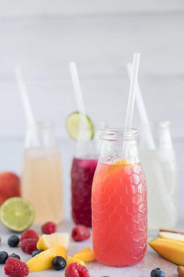 4 bottles of flavored water with blueberries, peaches and lime