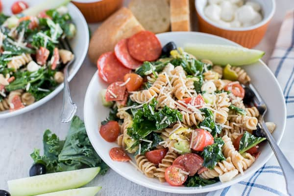 pasta salad with olives, pepperoni, cheese, kale, and cucumber in a white bowl