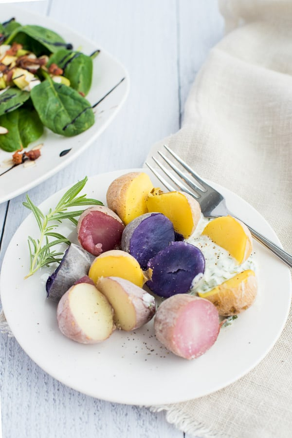 Purple, yellow, and white potatoes on a white plate with a creamy sauce