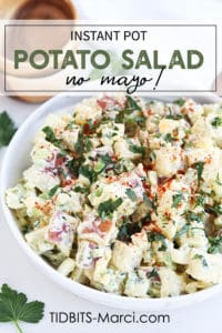 Potato Salad in a white bowl topped with herbs and paprika