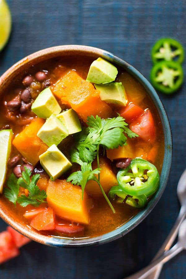 butternut squash chili in a brown bowl with jalapeno peppers