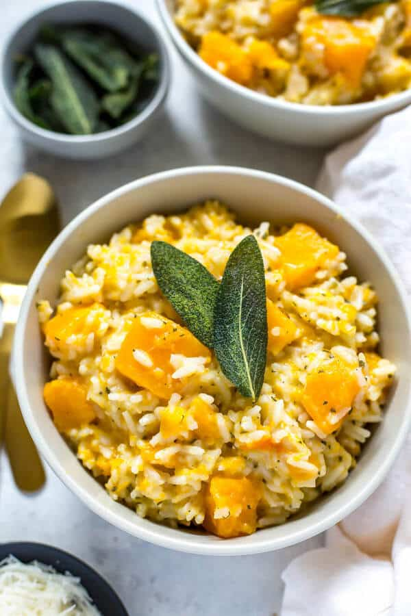 butternut squash risotto in a white bowl with sage leaves