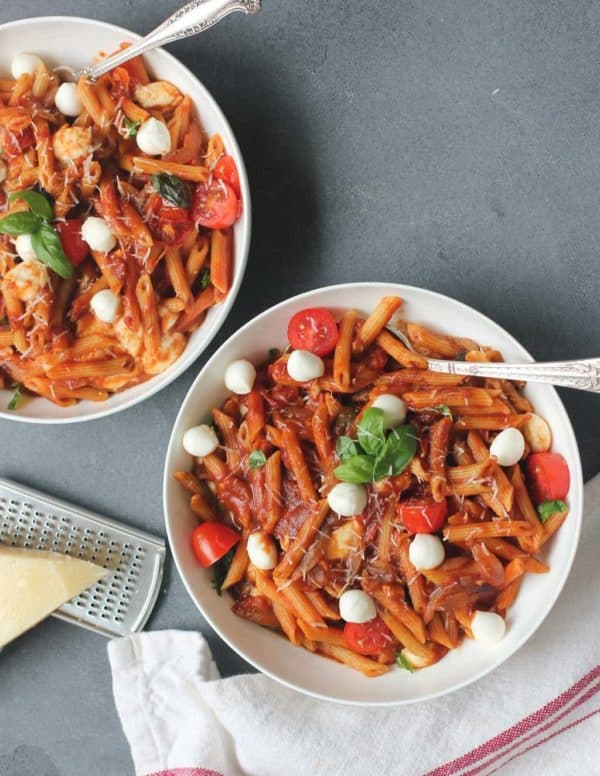 Bowl of pasta with tomatoes, basil, and mozzarella
