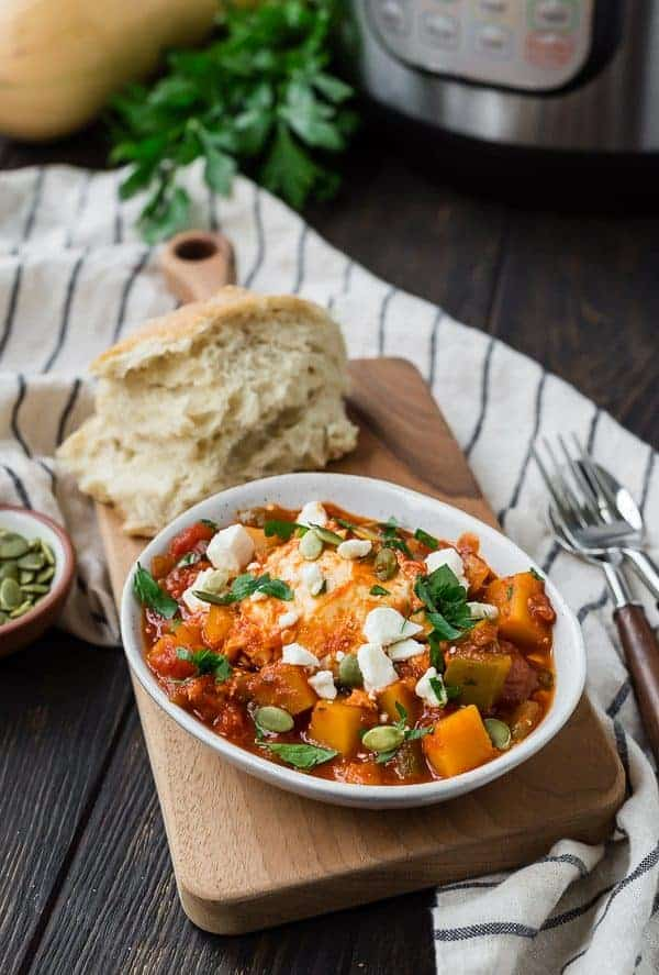 Butternut squash shakshuka in a white bowl with bread