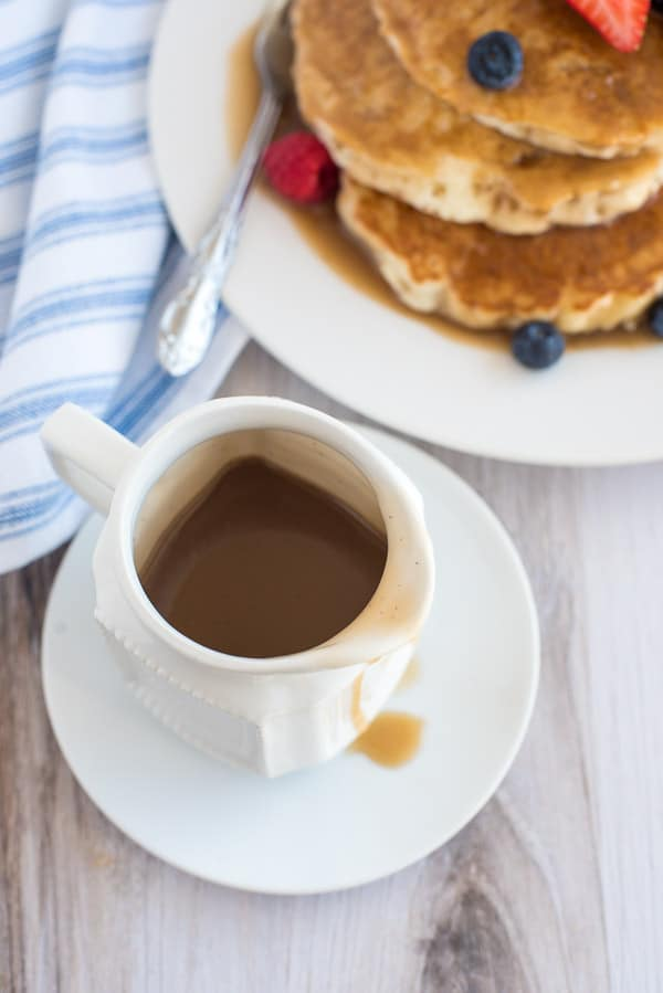 Cinnamon Syrup in a white cup on a white plate with pancakes in the background