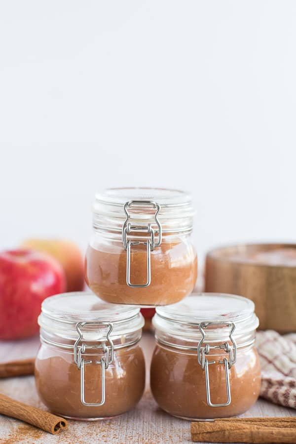 applesauce in clear jars with apples in background