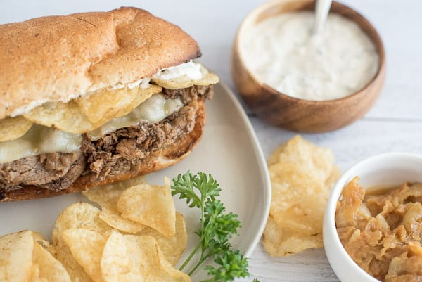 French dip sandwich on a plate with chips and horseradish sauce
