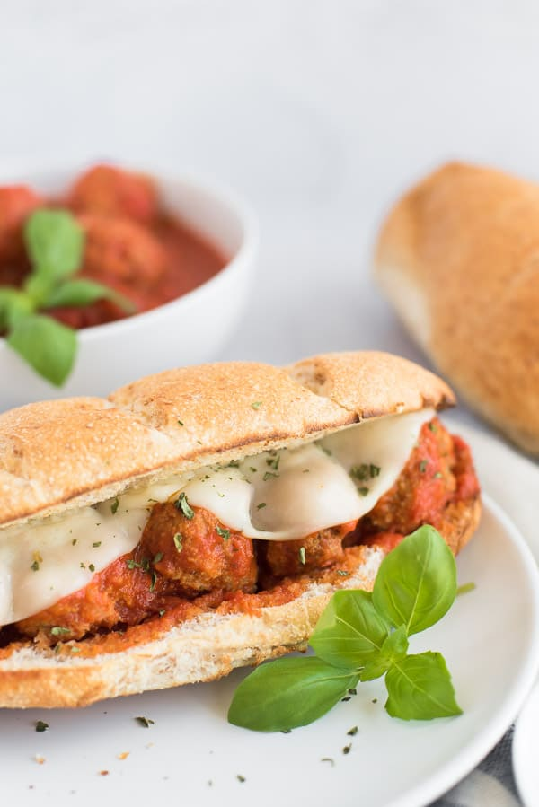 meatball sandwich on a white plate with basil