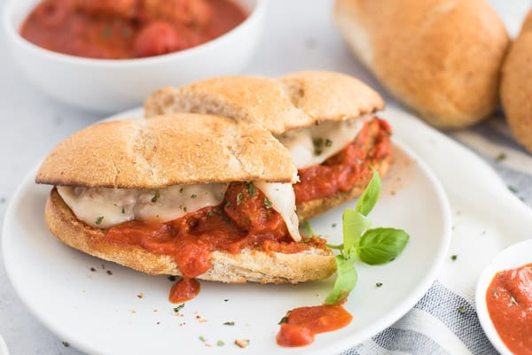 meatball sandwich cut in half on a white plate with basil