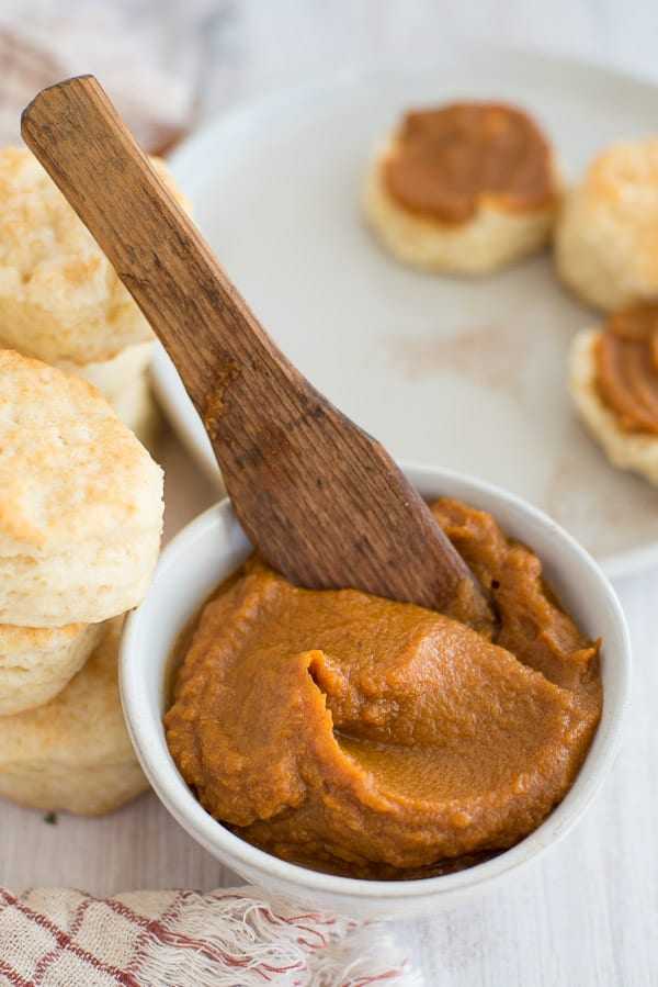 pumpkin butter in a white bowl with a spoon and biscuits on the side