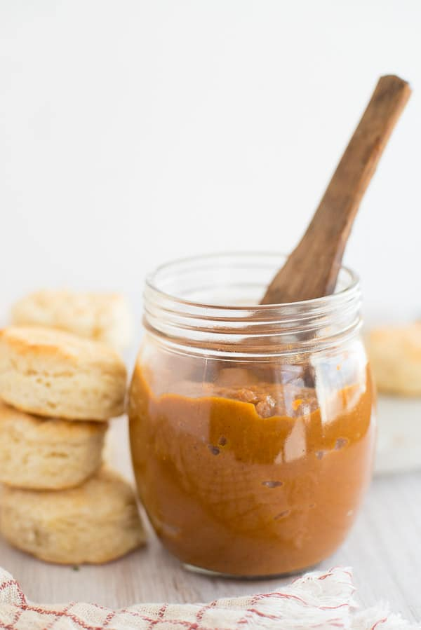 pumpkin butter in a jar with a spoon and biscuits on the side