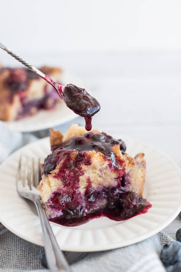 Stuffed French Toast on a white plate covered in blueberry sauce