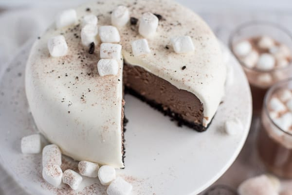 Chocolate cheesecake with white ganache on a white plate with marshmallows
