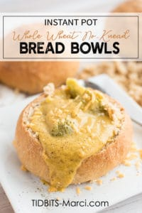 Bread bowl with broccoli cheese soup on a white plate