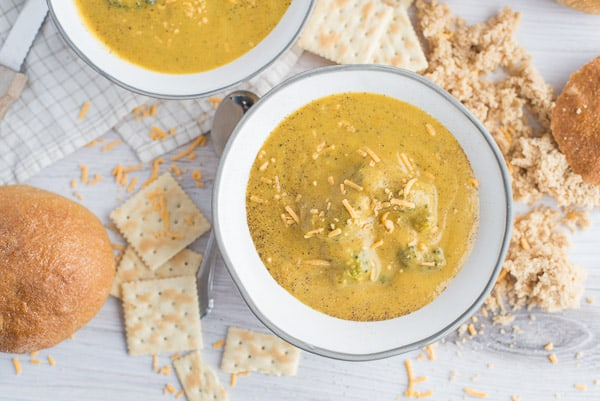 Broccoli Cheddar soup in a bowl with cheddar cheese on top and crackers