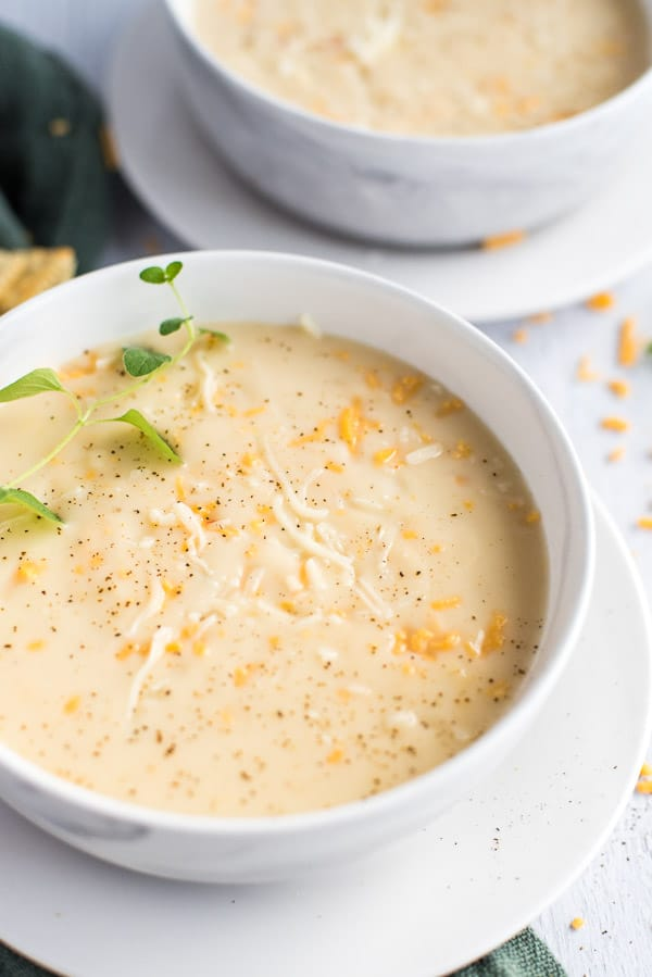 instant pot cauliflower soup in a white bowl with cheese and herbs