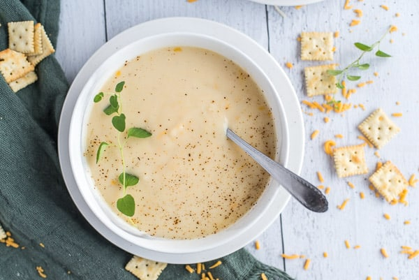 instant pot cauliflower soup in a white bowl with cheese and herbs and a spoon