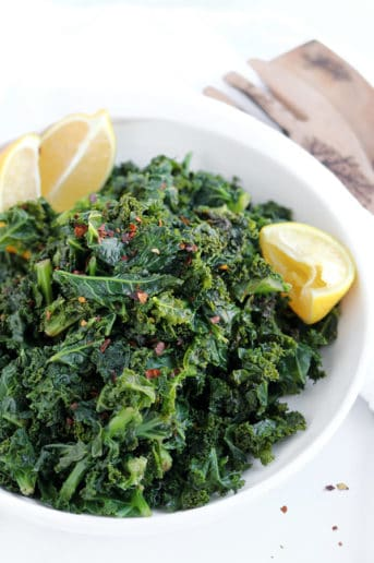 kale with lemon in a white bowl