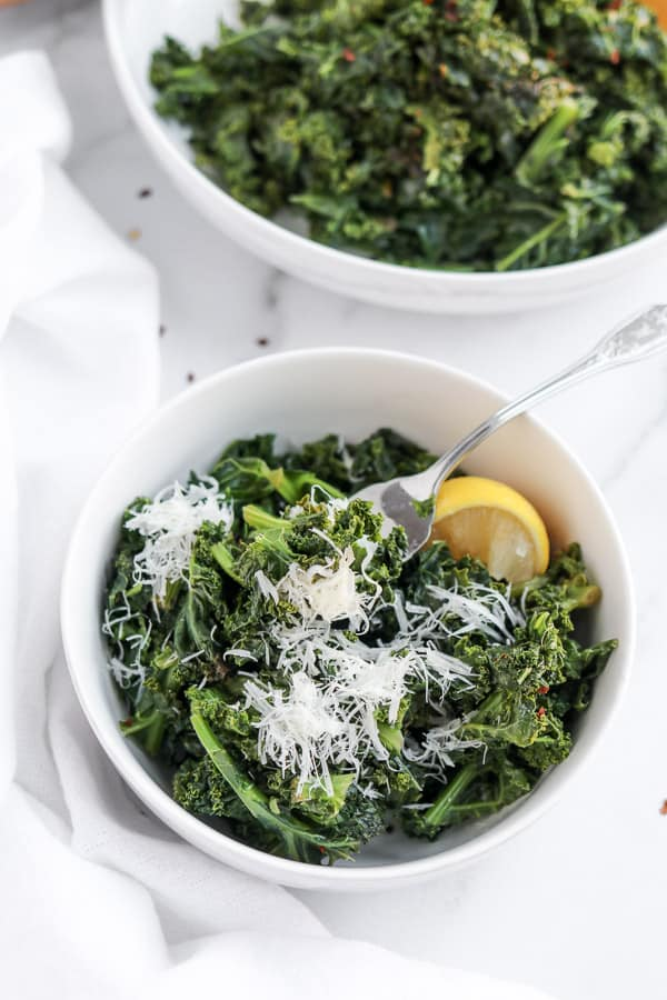 kale with lemon and parmesan in a white bowl