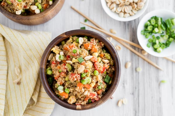 brown bowl with quinoa, peas, corn, and edamame with chopsticks