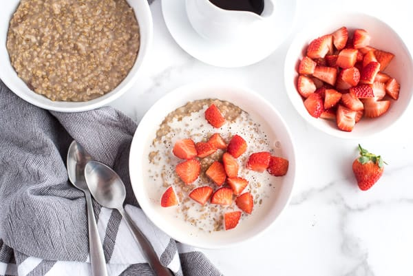 bowl of steel cut oatmeal with strawberries and cream and a cup of chocolate