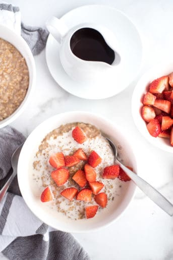 bowl of steel cut oatmeal with strawberries and cream and a bowl of strawberries