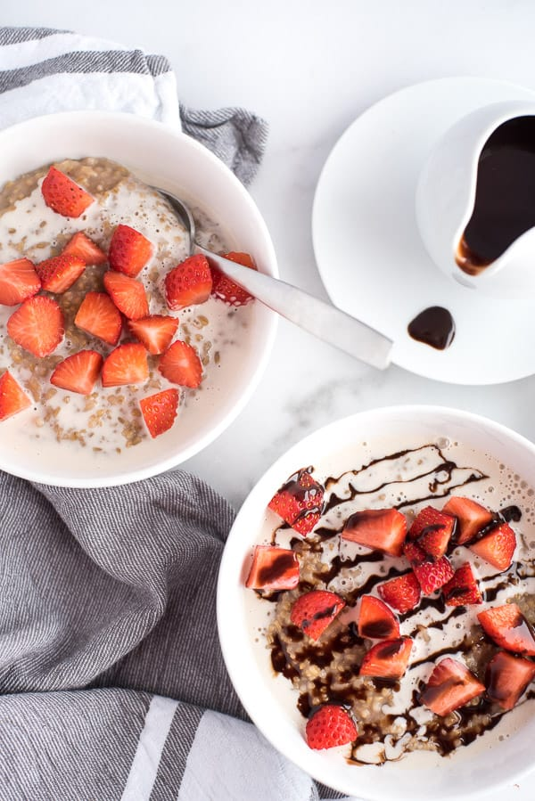 2 bowls of oatmeal, one with strawberries and chocolate and one with just strawberries