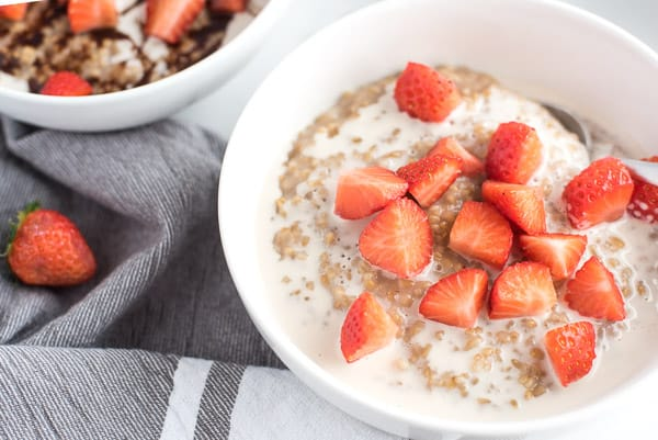 Bowl of oatmeal with fresh strawberries on top in a white bowl