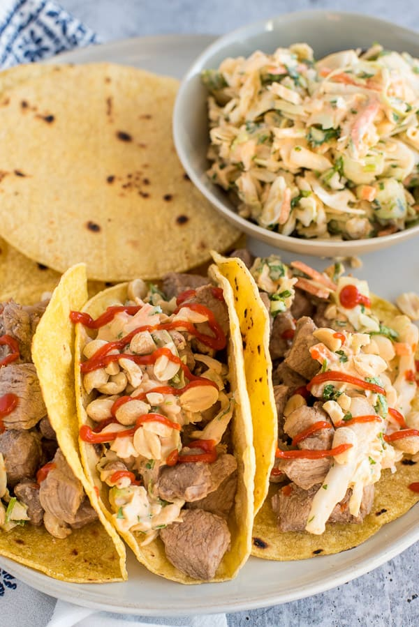 three tacos filled with pork and coleslaw drizzled with hot sauce