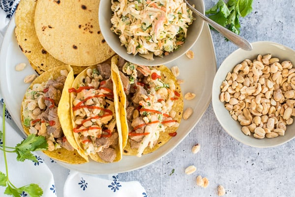 three tacos filled with pork and coleslaw drizzled with hot sauce and peanuts