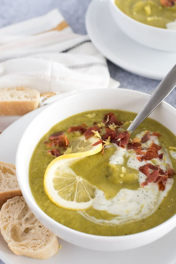 Green asparagus soup with yogurt, bacon, and a lemon slice in a white bowl