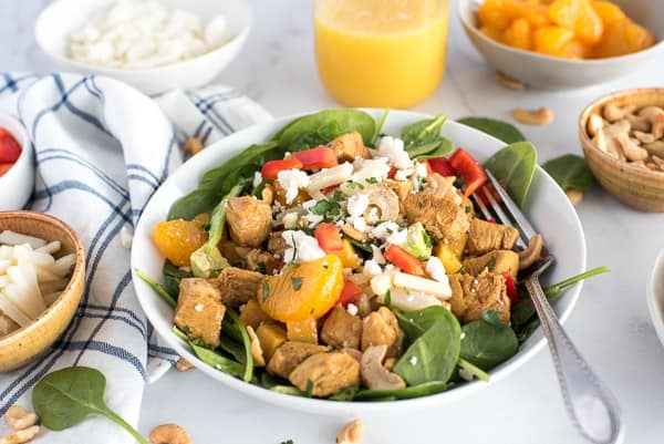 bowl of spinach salad with chicken, bell peppers, mandarin oraanges, and cheese with orange vinaigrette