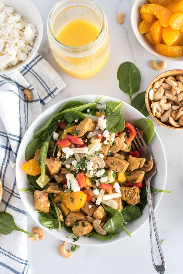 bowl of spinach salad with chicken, bell peppers, mandarin oraanges, and cheese with a bowl of cashews